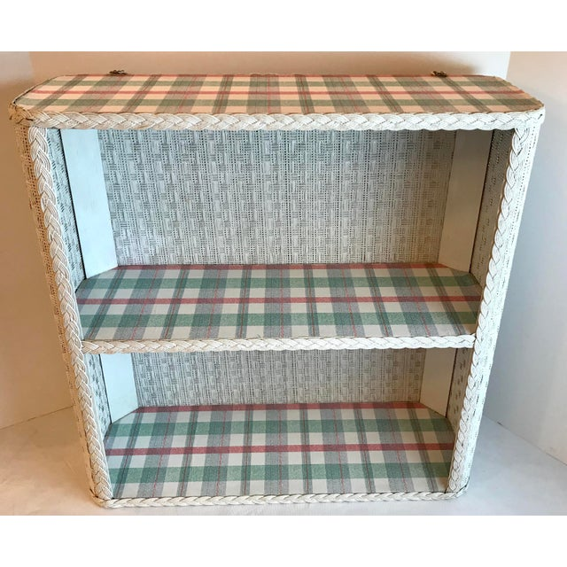 Nice vintage white wicker wall shelf with a plaid lining on the shelves. Made in the mid 20th century.