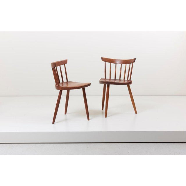 Vintage version of a pair of the Mira Chair by George Nakashima. The chairs are in walnut. One bottom of the seat still...