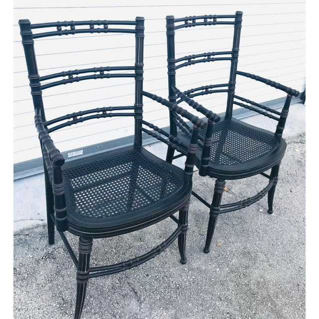 Stunning 2 vintage baker furniture faux bamboo chairs. Color black with brown accent. In very good condition.
