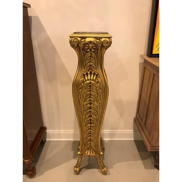Stunning pair of Mid-Century Modern giltwood pedestals with marble tops. Hand-carved giltwood bases. Having green and...