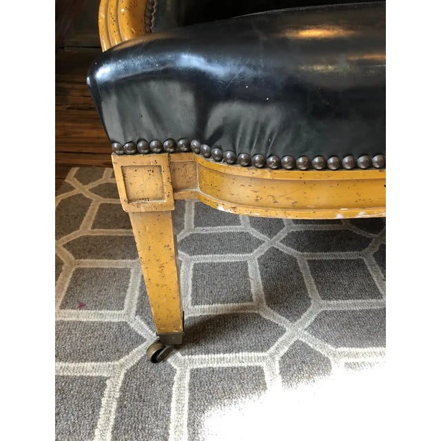 A wonderfully shaped loveseat having handsome fruitwood frame and sexy black faux leather upholstery finished with...