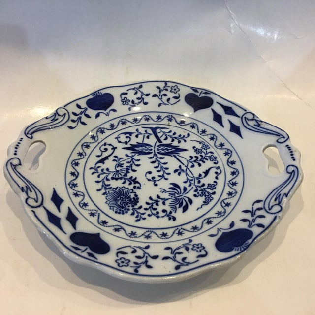 A beautiful blue and white porcelain serving dish with handles. Floral and fruit stylized Designs. A great decorative piece.