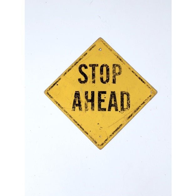 A vintage 'Stop Ahead' street sign. The American metal road warning sign is vibrant yellow with black wording. There are...