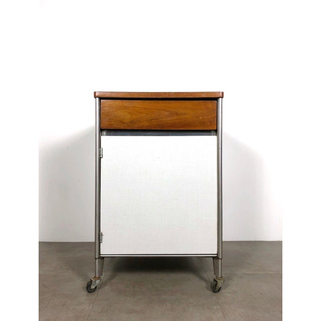 Rare industrial storage cabinet by Raymond Loewy for Hill-Rom, 1950's. Walnut and patterned laminate on casters, with...