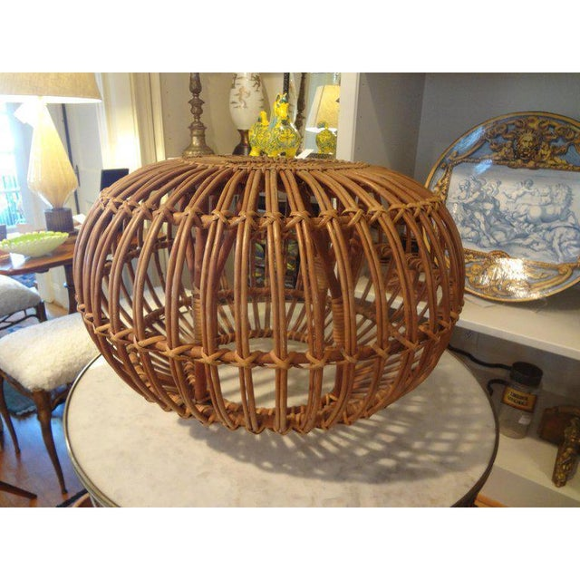 Mid-20th century woven rattan ottoman, pouf or stool designed by Franco Albini. This versatile Hollywood Regency piece...