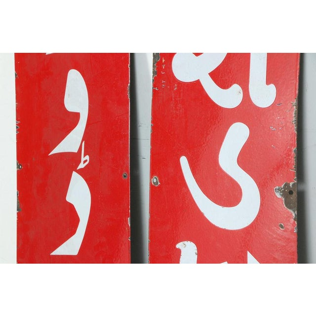 A pair of metal signs. These two sheet metal signs have red backgrounds with white letters. The sign to the left reads...