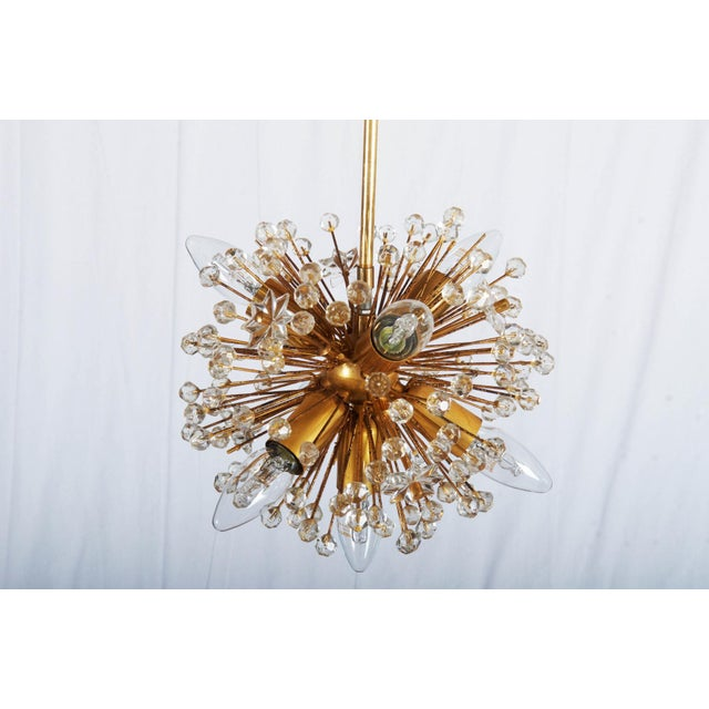 This gold-plated Sputnik chandelier from the early 1970s was made in Vienna by Emil Stejnar for Rupert Nikoll.