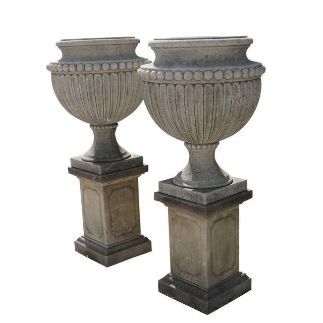Early 20th century, a pair of finely carved limestone urns, having circular socle and square base. The Campana shaped...