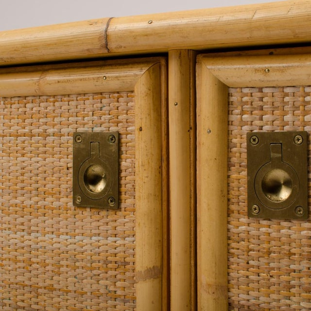 A unique Italian rattan server, circa 1960, fronted by a pair of doors opening up to large storage area with shelves. Each...