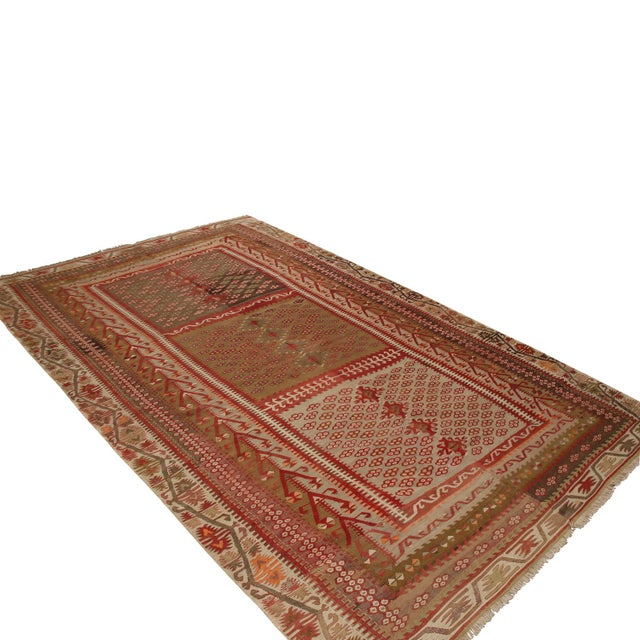 Originating from Turkey between 1940-1950, this vintage Kayseri wool Kilim rug features a high-quality flat weave and a...
