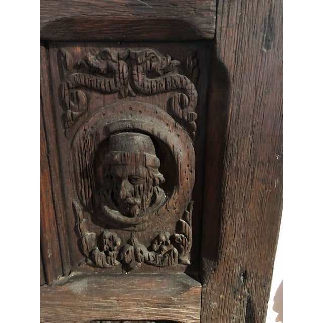 English hand-carved dark oak door with various characters faces and lower folded linen design circa 1700, England.
