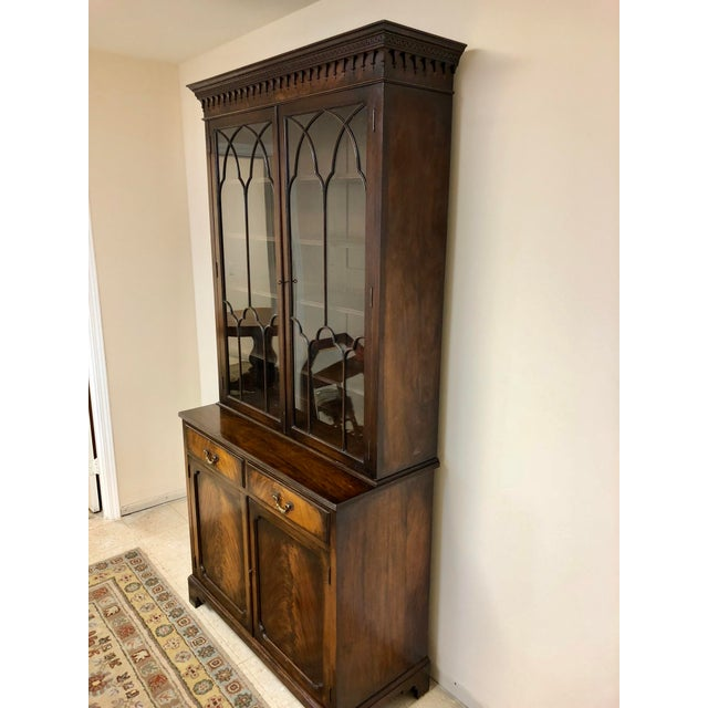 A beautiful Georgian Step-back Bookcase Cabinet in burl walnut with Moorish arch glass doors and beautiful crown molding....