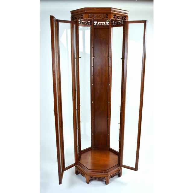Beautiful rosewood curio cabinet in an octagonal shape with glass panels on seven sides and one rosewood back panel....
