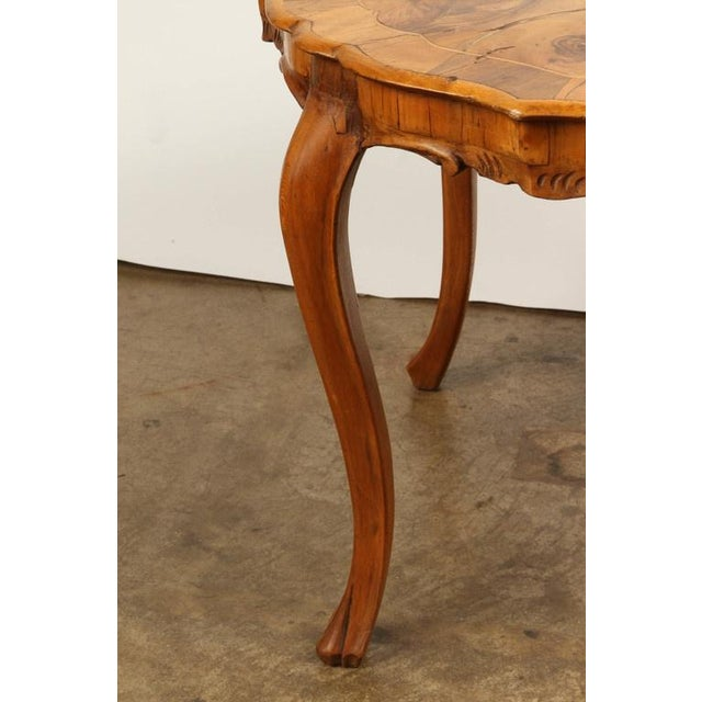 A Danish walnut inlaid side table, with subtly scalloped top and four curved legs with carved feet.