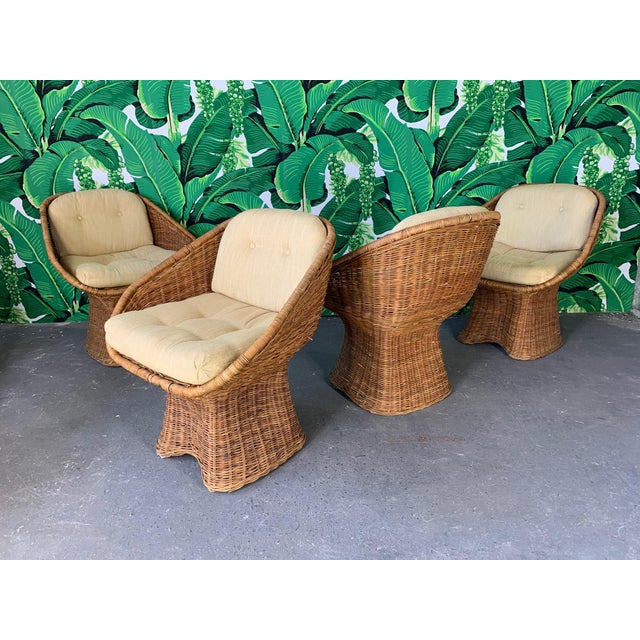 Set of four sculptural wicker dining chairs feature unique draped pedestal and scoop shape seat. Cream fabric in good...
