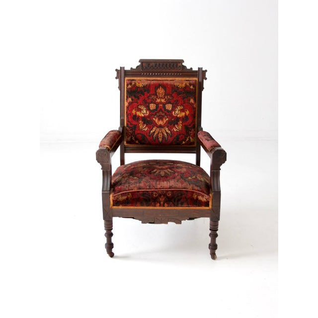 This is an antique Sheraton style upholstered arm chair. The dark wood chair features turned legs with casters. Rich...