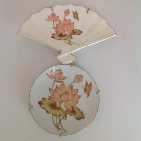 This porcelain fan-shaped plate has peach lotus blossoms and buds on a creamy white background edged in gold leaf. Its...