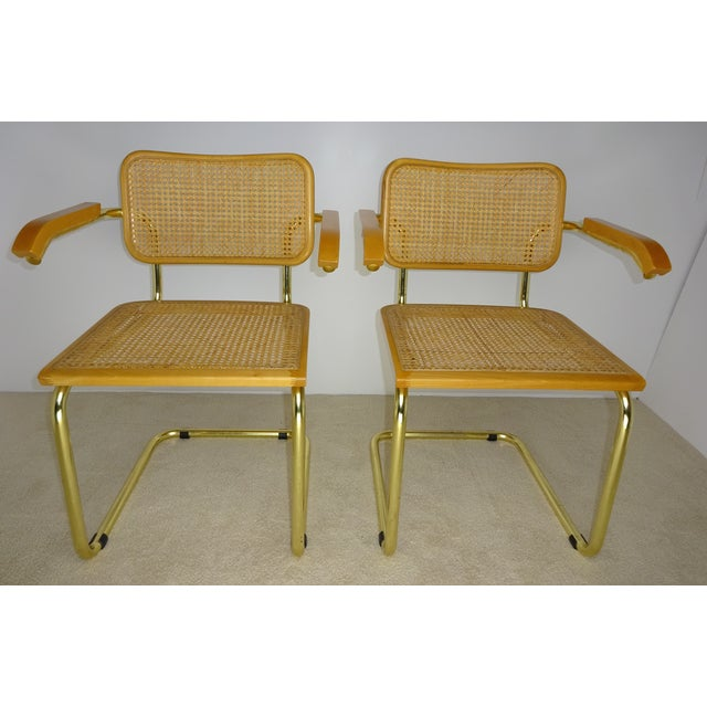 A pair of quality Italian brass plated tube arm chairs with cane backing/seating and beech arms designed by Marcel Breuer....
