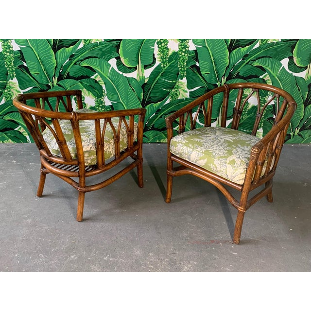 Pair of bamboo accent chairs finished in deep brown with a tropical print upholstery. Includes seat and back cushions....