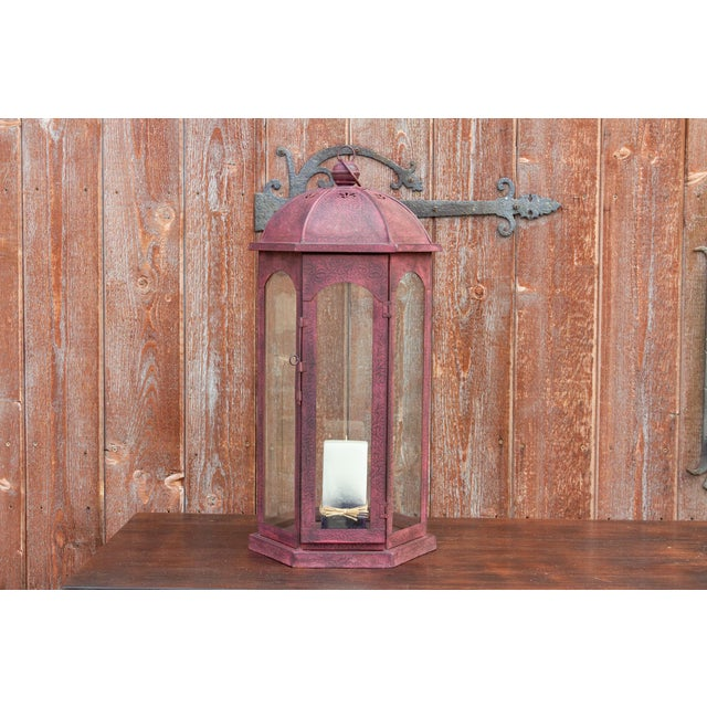 This handmade metal lantern provides ambient light with its glass paned sides, and embossed metal painted frame. The front...