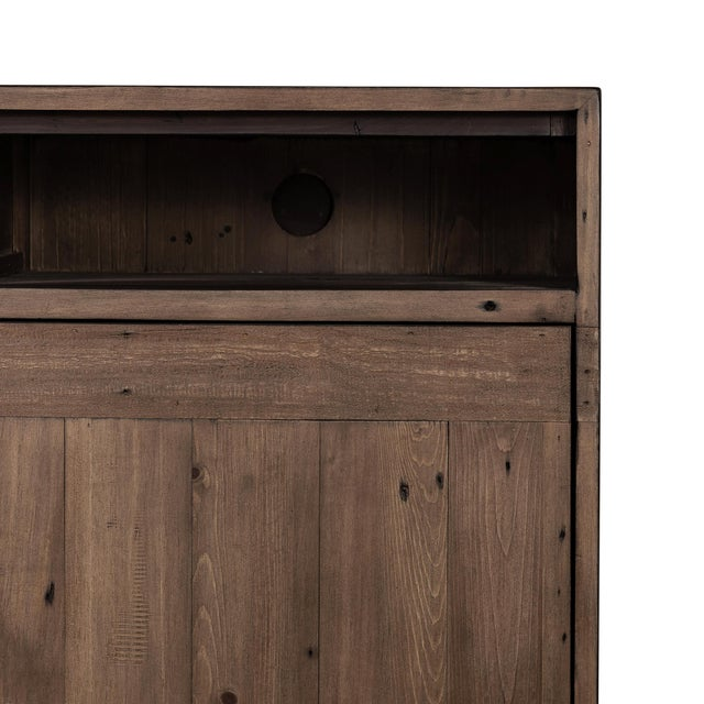Simple, streamlined style, with rustic undertones. Atop a plinth base, a media cabinet of FSC-certified woods features...