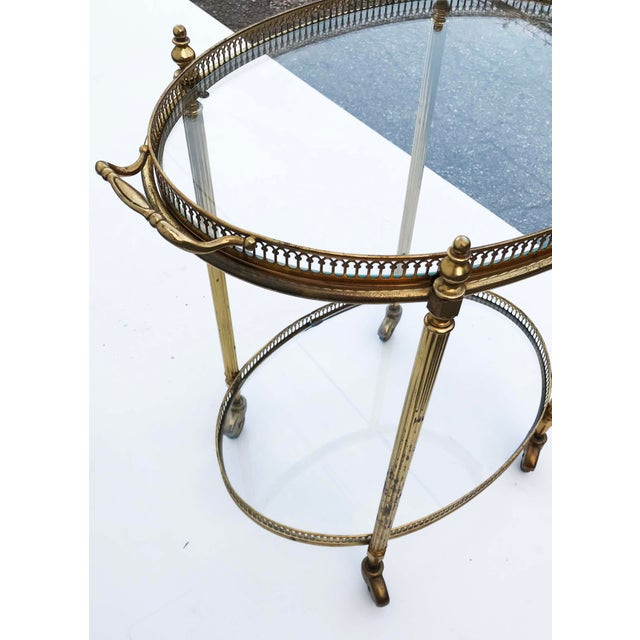 Maison Bagues oval bar cart in its original condition. some wear. 2 clear glass in good condition. Elegant brass gallery