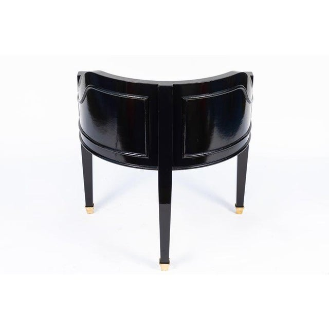 Pair of midcentury Hollywood Regency style black chairs. Black lacquered with molding detail with bronze cap feet.