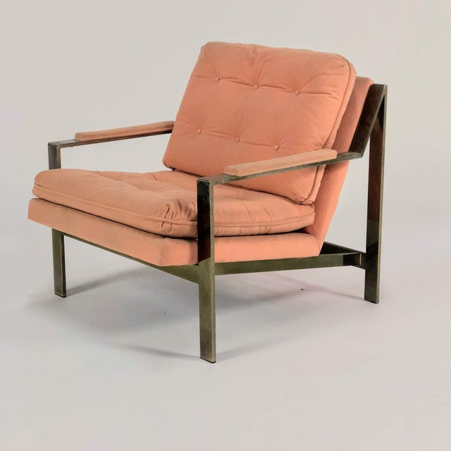 A mid-century modern gold toned chrome wide bar lounge chair with loose tufted cushions, covered in peach colored...