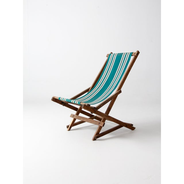 Bold green stripes color this vintage American deck chair. The outdoor chair has a rocking wood frame and a striped canvas...
