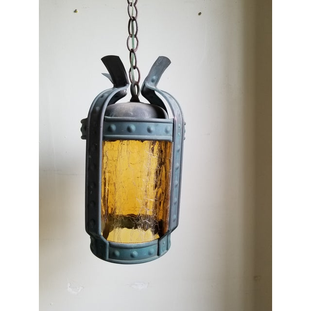 Antique Art & Craft Era copper hanging lantern with a verdigris patina finish and an amber crackle glass cylinder shade....