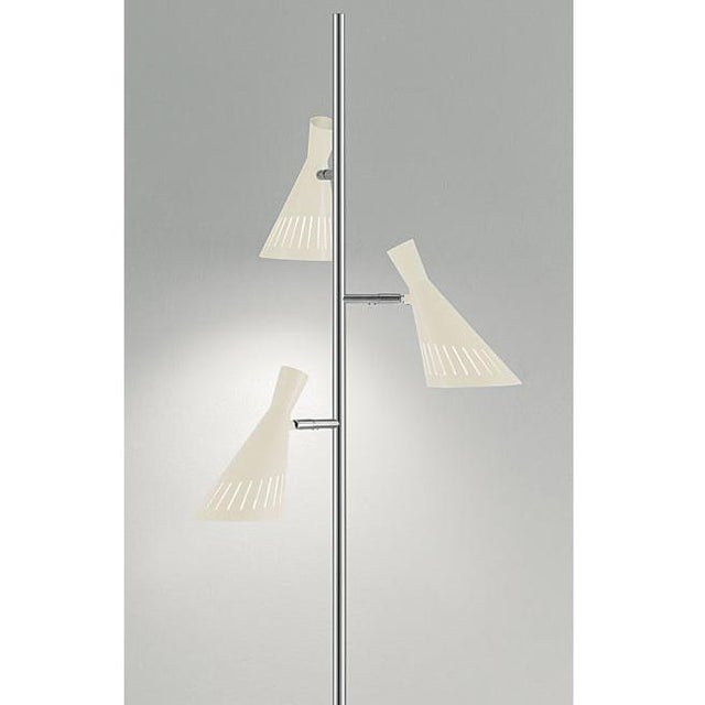 Ivory with polished chrome floor light with 3 lamp heads. The shades have decorative slots to allow light spill. Warm LED...