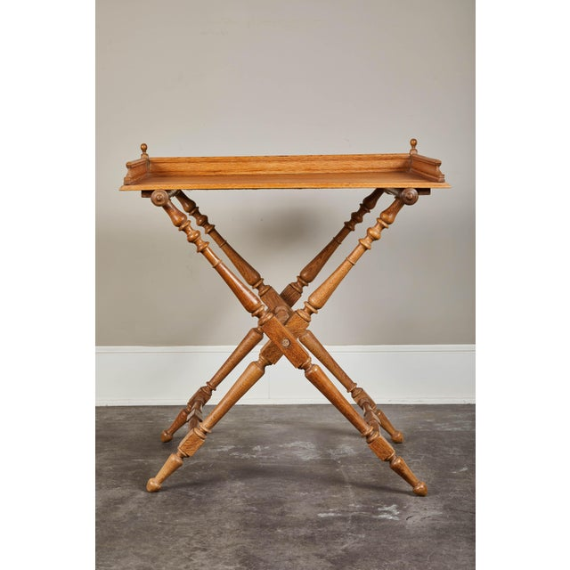 An oak tray on a collapsible oak stand. Functional and gorgeous. Stand features turned legs and spindles with two fabric...