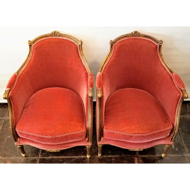 Pair Louis XV style bergere chairs from the 1920s. Carved gilt wood frames with shaped handholds, carved bow topping the...