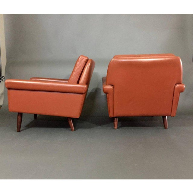 A classic pair of lounge chairs with beautifully squared arms and tampered back with two loose and buttoned cushions - all...