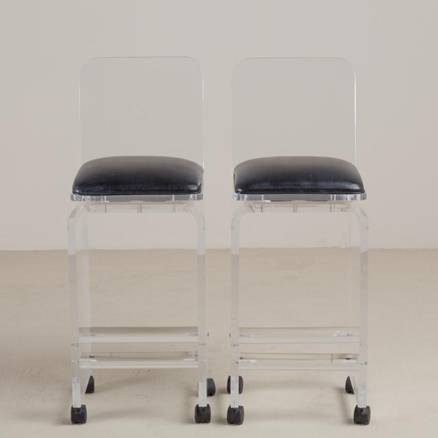 A Pair of Lucite Faux Leather Upholstered Swivel Bar Stools 1980s NB: These items are subject to a further discount over...