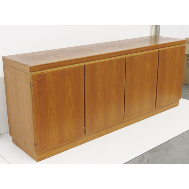 A sideboard that features 4 doors one end with shelves the other end with drawers.