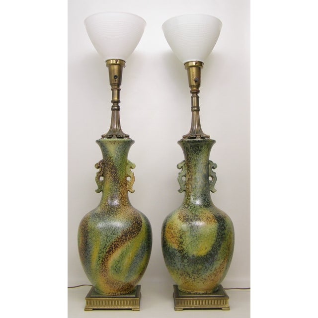 Large and impressive, this vintage pair of multi-colored ceramic table lamps is in the Asian style of James Mont. It...