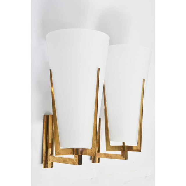 The frosted conical shade over a brass three pronged and armed structure.