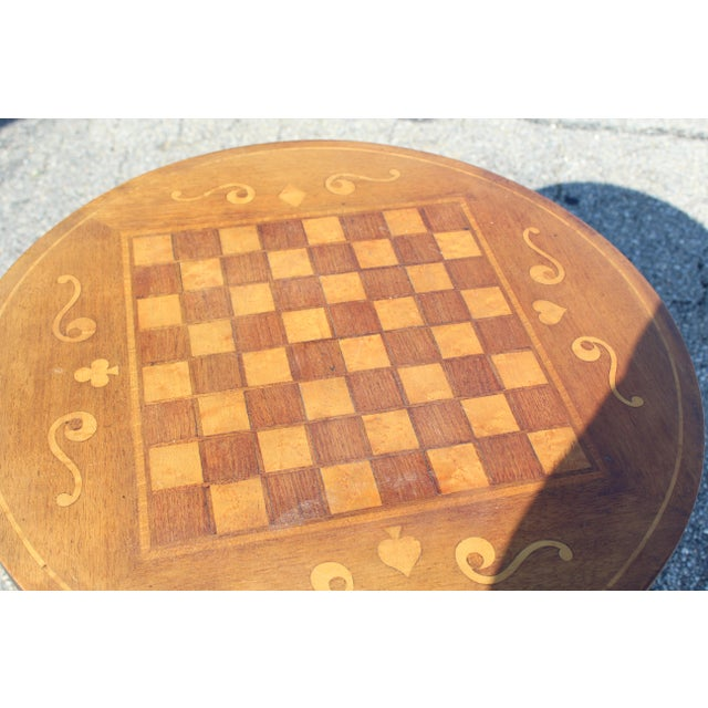 Circa 1900 hand crafted antique wooden inlaid game table with checker inlay. Four-footed base on a striped carved pedestal...