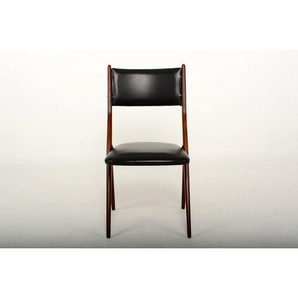 For your consideration a set of four mahogany armchairs with faux black leather. Sculptural scissor shape. Firm and...