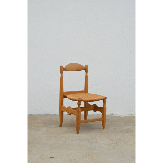 Rare set of 12 Guillerme et Chambron blond oak and rush chairs. Sturdy and comfortable.