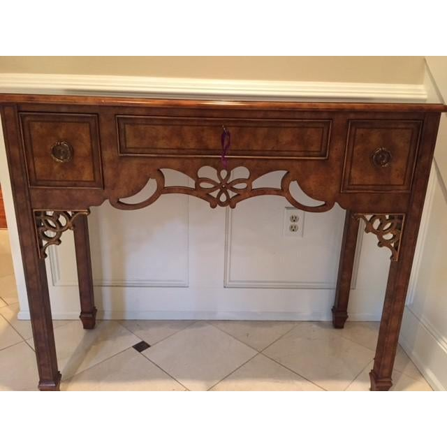 Maitland Smith- decorative console table with lightly golden accented filigree carved open designs. Three functional and...