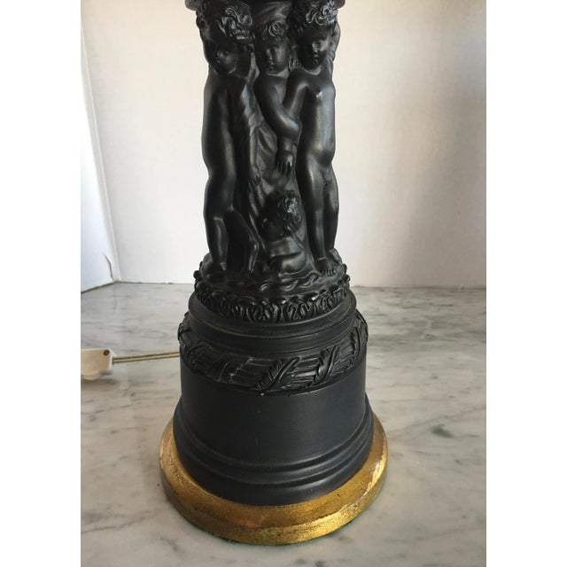 A stunning E.F. Chapman lamp of blackened plaster figurines. The figures are molded with facial expressions and movement....