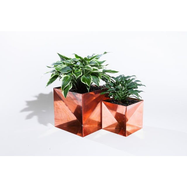 The Copper Origami Planter is an outdoor planter made from solid copper that will develop a rich green to brown patina in...
