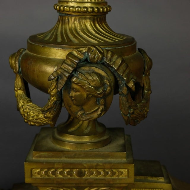 A set of antique French Empire andirons offer cast bronze in urn form with drape, flame, and central female mask elements,...