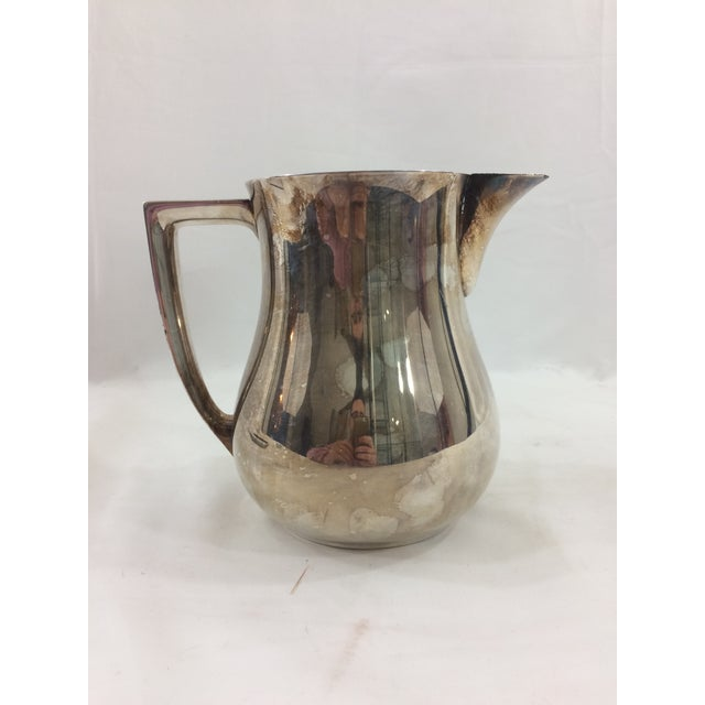 This sleek silver-plated pitcher makes a great accent for any lover of Mid-Century design. Marked on the bottom, this...