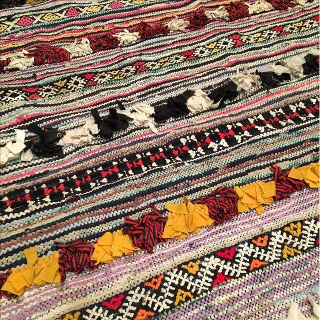 Offered is a textural rug in hues of bold black, pink, yellow, white and red with nubby stripes throughout. A rug pad is...