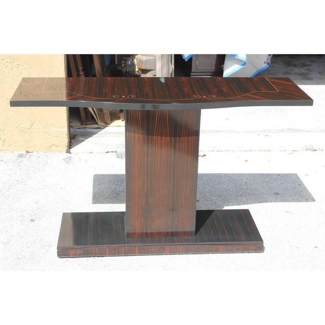 Classic French art deco exotic Macassar ebony console table. This features a delicate mother-of-pearl inlay detailing....