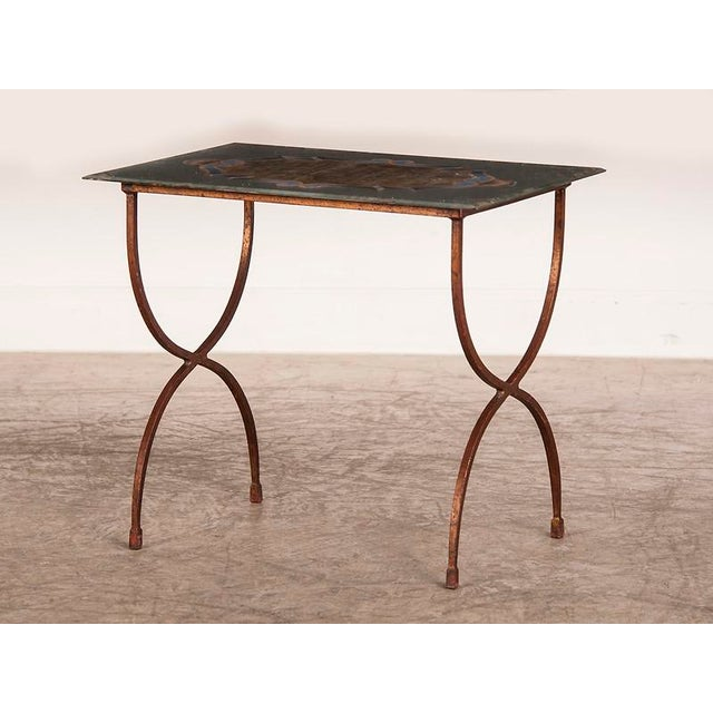 """An unusual curule shaped iron base table supporting the original """"verre-eglomise"""" glass top with an heraldic design from..."""