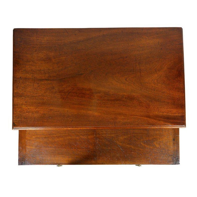 With rectangular top over a brushing slide and four graduated drawers, raised on bracket feet.